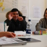 2 students in and English class smiling and speaking English with native English teacher at London language academy