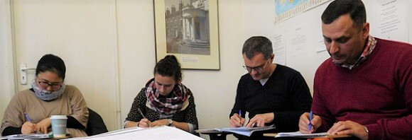 Four adults students of English writing in English class in London
