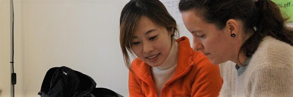 Two students in the class of ielts courses in London preparing for the IELTS exam