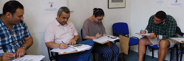 Four students writing IELTS task in the class of English Course for Adults