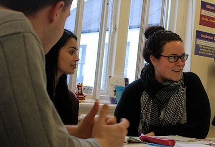Three students of an English course for adults talking and improving English