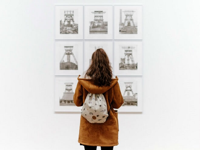 Tourist in London at an art exhibition looking at old photographs