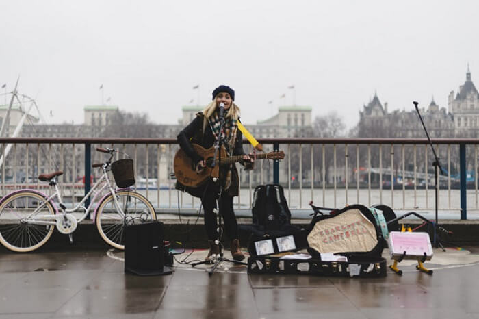 Female artist singing and playing live in London Southbank