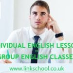 Student wearing a white shirt thinking about the choice between individual English lessons and group classes