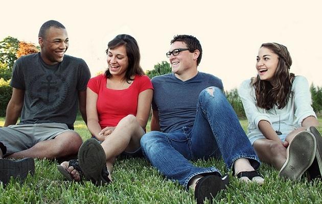 Four international students of English language practising English conversation skills outdoors