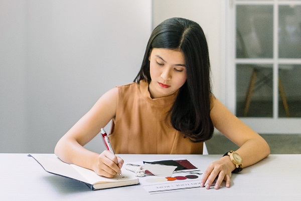 A female student writing in a notebook preparing for the Academic IELTS test