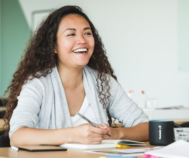 Female student on a study for IELTS course writing IELTS essay task and smiling